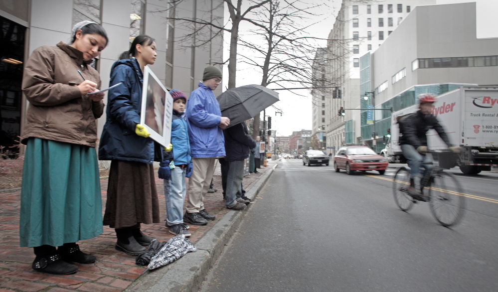 Anti-abortion protesters stand across the street from the Planned Parenthood clinic in Portland on Nov. 22, 2013, the first day they picketed the Congress Street clinic since a 39-foot buffer zone around the clinic took effect.