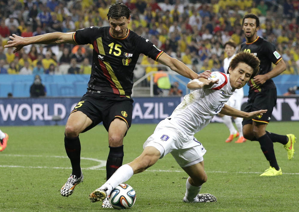 Belgium's Daniel Van Buyten, left, and South Korea's Koo Ja-cheol  challenge for the ball during the group H World Cup soccer match between South Korea and Belgium at the Itaquerao Stadium in Sao Paulo, Brazil, on Thursday.