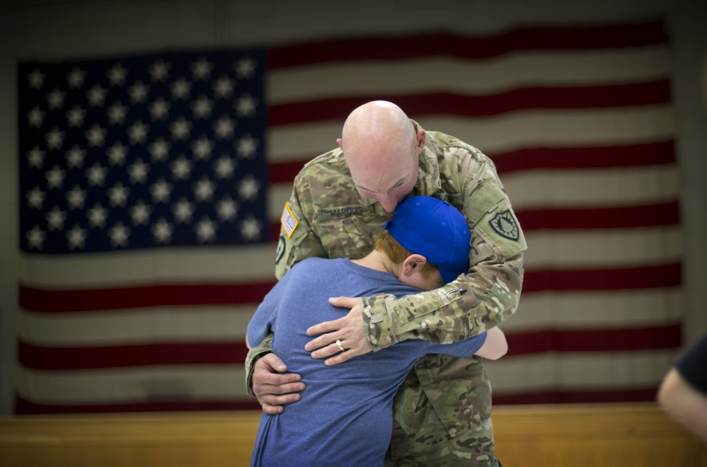 Andrew Marquis gets a hug from his nephew, Ryan Verrill of Lewiston, Maine, after members of the Maine Army National Guard's 133rd Engineer Battalion returned home from Afghanistan on Friday in Augusta. Marquis, formerly of Lewiston, now lives in Boston, Mass.