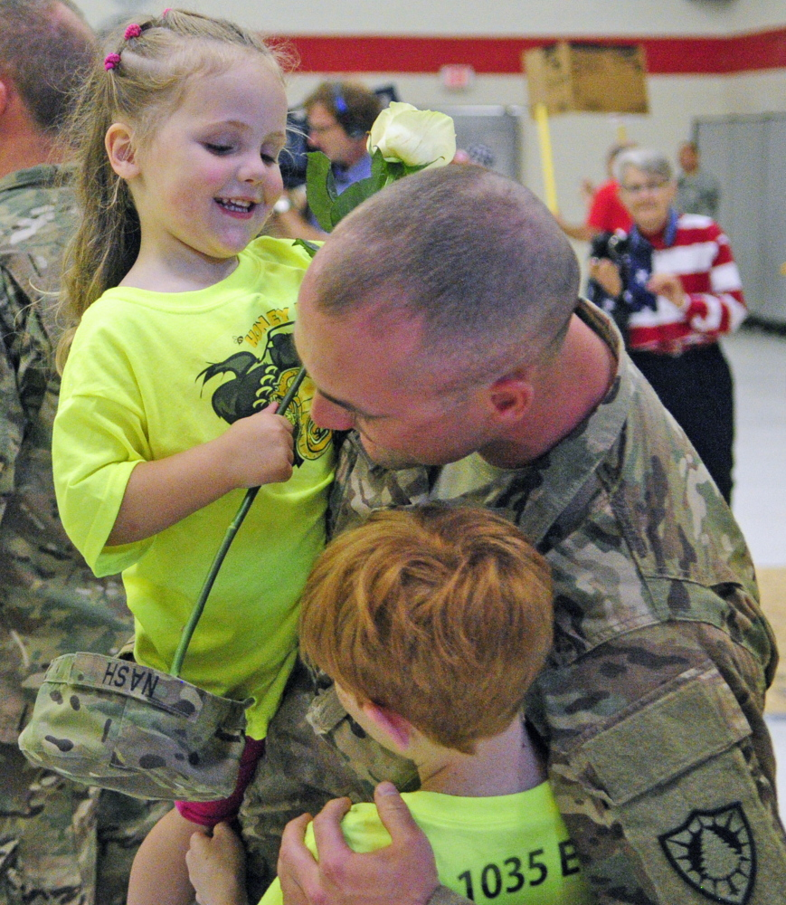 Sgt. Casy Nash, center, hugs his daughter Althea Nash, 2, top, and brother Kyle Nash, 10,  on Friday at the Augusta Armory. He had a large group of his family from Eddington there to greet him when he and the 1035th Survey and Design Team returned from Afghanistan.