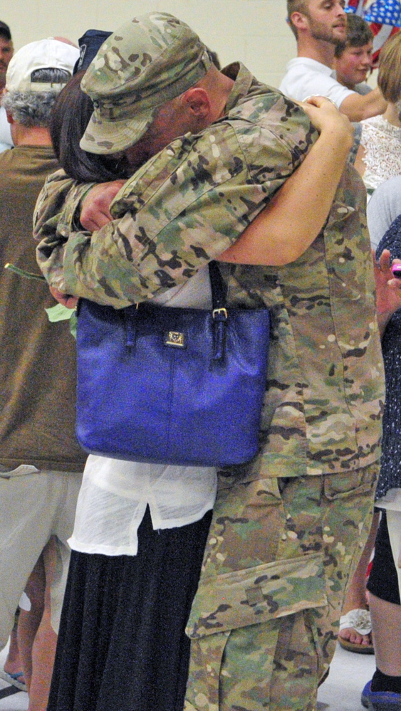 Nicole Mailhot, left, hugs Staff Sgt. Todd Perkins after he and the 1035th Survey and Design Team returned from a deployment in Afghanistan on Friday at the Augusta Armory.