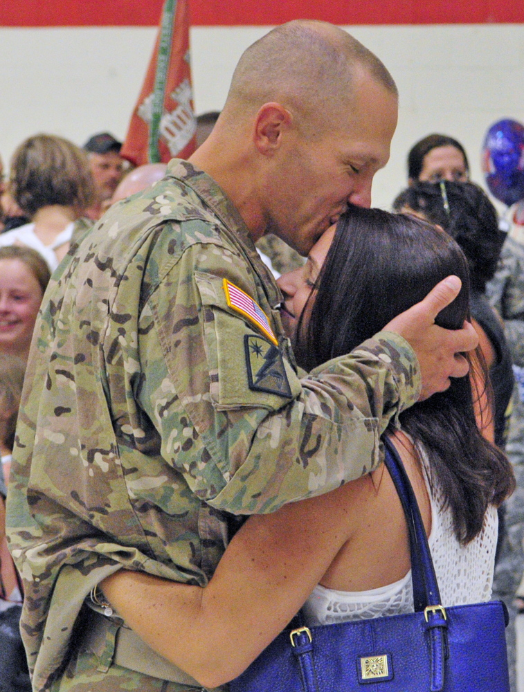 Staff Sgt. Todd Perkins kisses Nicole Mailhot, after he and the 1035th Survey and Design Team returned from a deployment in Afghanistan on Friday at the Augusta Armory.