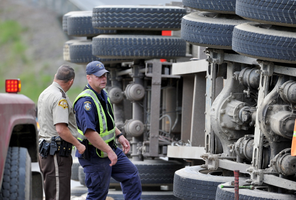 Investigators inspect a logging truck that flipped and hit an SUV on U.S. Route 201 in Moscow on Thursday. Police said Friday speed and a blown tire on the truck probably caused the crash.