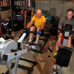 Dave Grody, left, and Dan Benson work out on two different kinds of rowing machines Friday in China. They were alternating machines every three minutes during their morning workout.