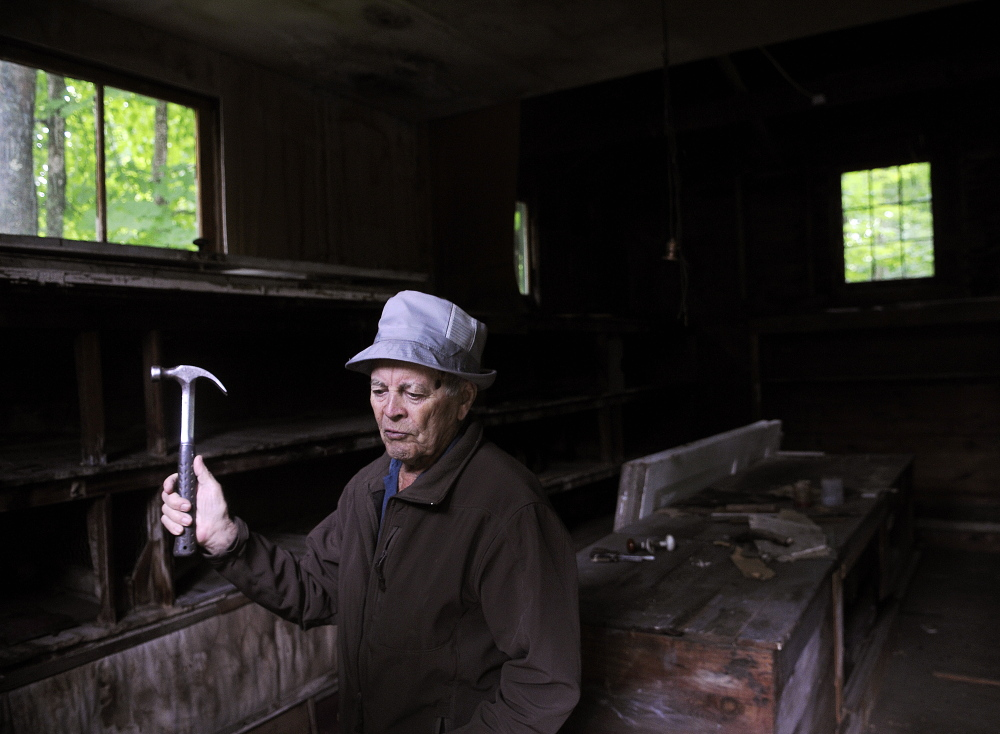 Lloyd McCabe, 90, repairs the former rabbit hutch Thursday that he recently purchased near his farm in Monmouth. McCabe plans to donate the small structure and the land along Mud Stream to the town for a park.