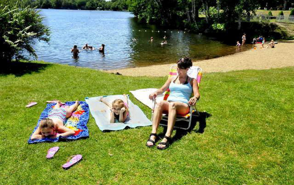 After the removal of Canada geese last week at the beach and boat launch on Messalonskee Lake in Oakland, the area should be cleaner with fewer droppings from the birds. Relaxing on a warm Monday from left are Madison and Izzy Drake and Tracy Liberty.