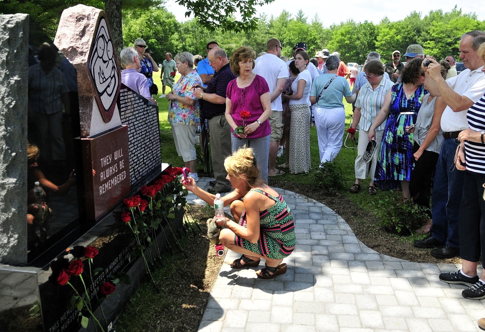 Survivors place roses in front of the Maine Murder Victims' Memorial Monument at the end of the dedication ceremony on Sunday in Augusta.