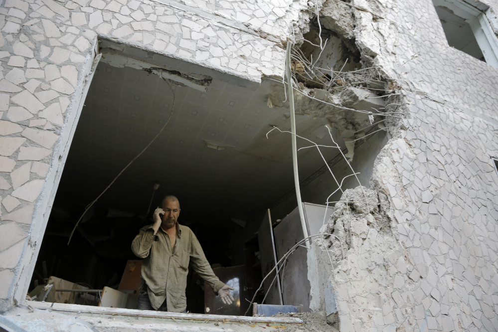 Valery, who gave only his first name, makes a phone call from a room of his damaged house after shelling in the city of Slovyansk, Donetsk Region, eastern Ukraine on Monday.