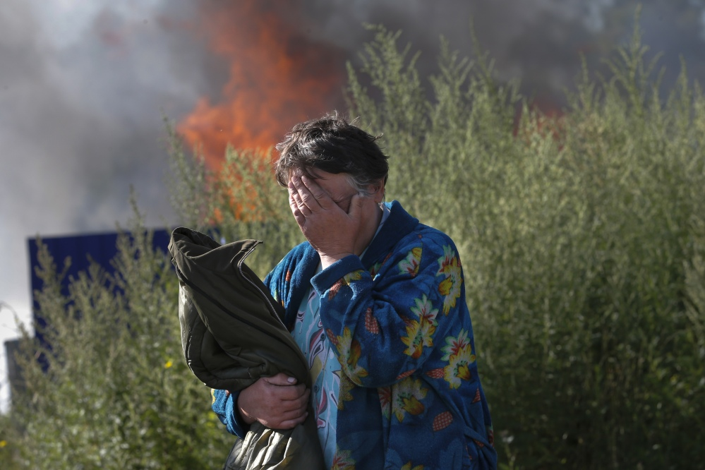 A woman cries near her burning house after shelling in the city of Slovyansk, Donetsk Region, eastern Ukraine, on Monday.