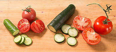 """Olivia's Garden tomatoes and cucumber purchased at the farmers market, left, and Shaw's vegetables, right. In her comparison, writer Susan Axelrod found that her money went further at Shaw's – """"everything I bought was simply bigger."""""""