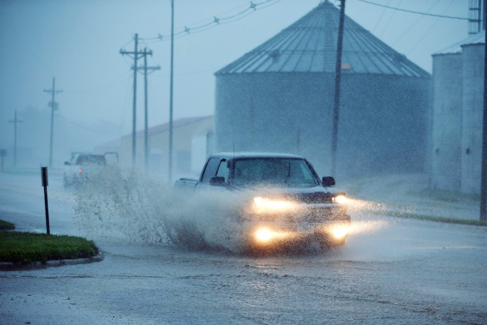 The Associated Press A truck drives through high water in Arlington, Neb., Tuedsay.