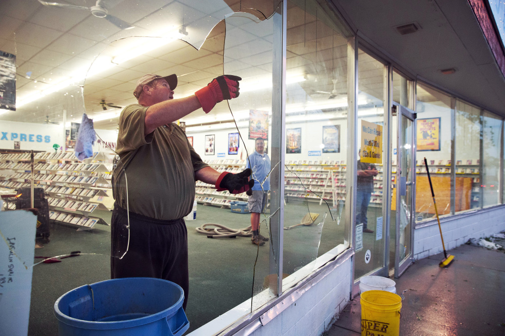 The Associated Press Garry Yanke, the owner of Video Express, cleans up the broken glass at his business in Blair, Neb.