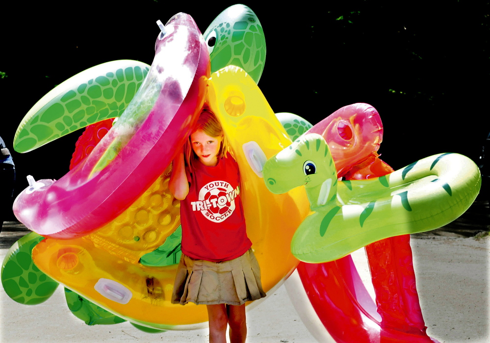 Hannah Fuller has her hands full carrying a half a dozen inflated water tubes toward the beach at Lake George Regional Park East in Canaan recently.