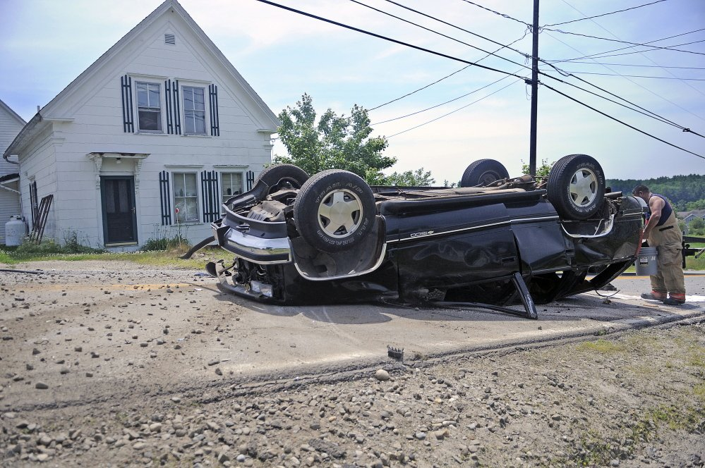 A firefighter contains fluids Tuesday from an SUV that rolled over and injured the driver.  Police say a single occupant of the vehicle was transported by helicopter to a trauma center after the accident occurred on Route 24 just after 11 a.m.