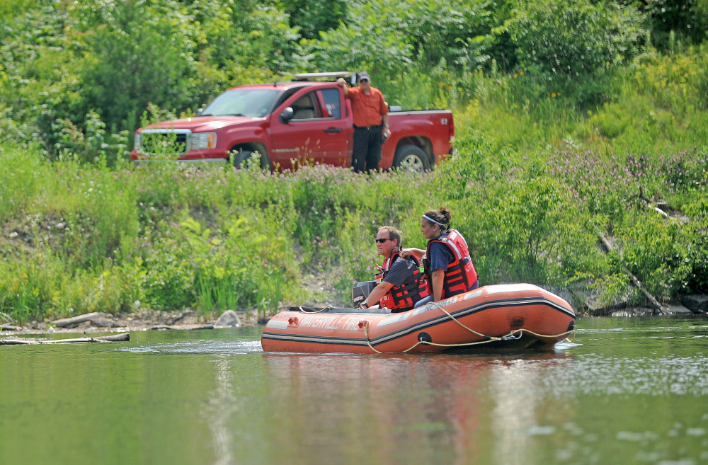 Firefighters from Waterville Fire Department search the area around a dam on the Messalonskee Stream for 82-year-old Wesley Johnston, who went missing Tuesday morning but was found later that evening.