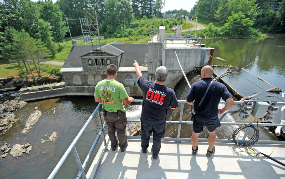Waterville Fire Department firefighters search the area around a dam on the Messalonskee Stream on West River Road in Waterville Tuesday for Wesley Johnston, 82.