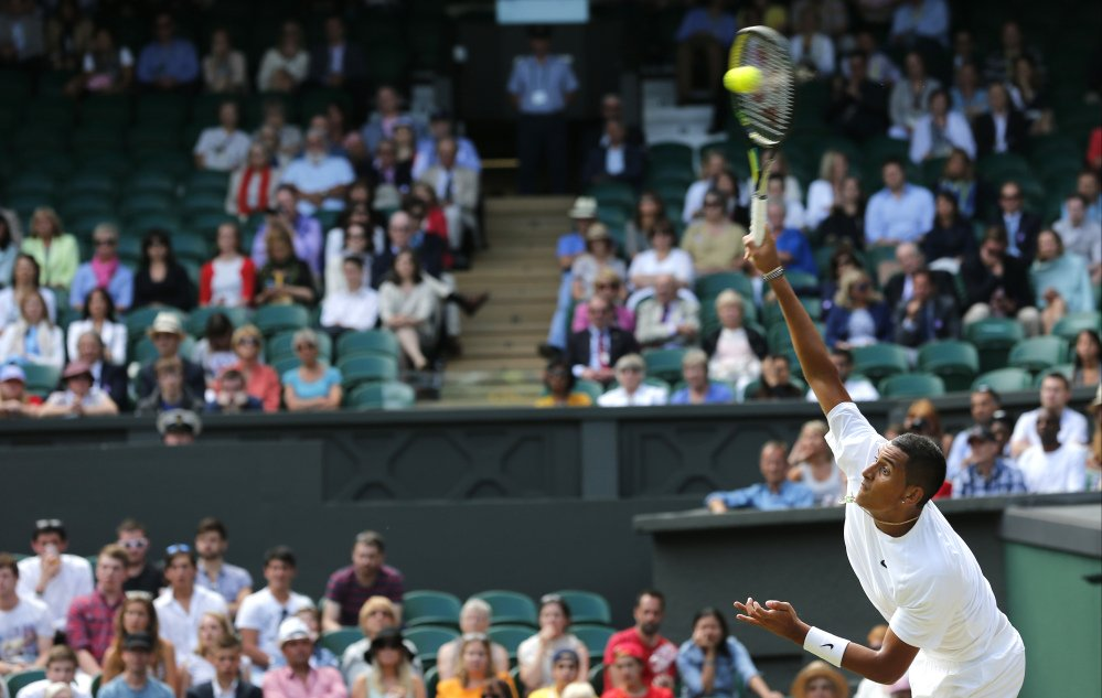 Nick Kyrgios of Australia serves to Rafael Nadal of Spain during their men's singles match at the All England Lawn Tennis Championships in Wimbledon, London, Tuesday, July 1, 2014.
