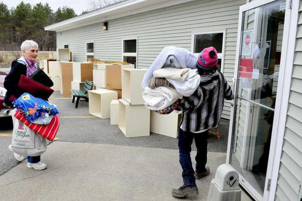 Waterville Humane Society worker  Luis Mauser holds the door for Jane Bird who donated bedding in April after boxes and bedding for animals were removed and destroyed following an outbreak of ringworm.