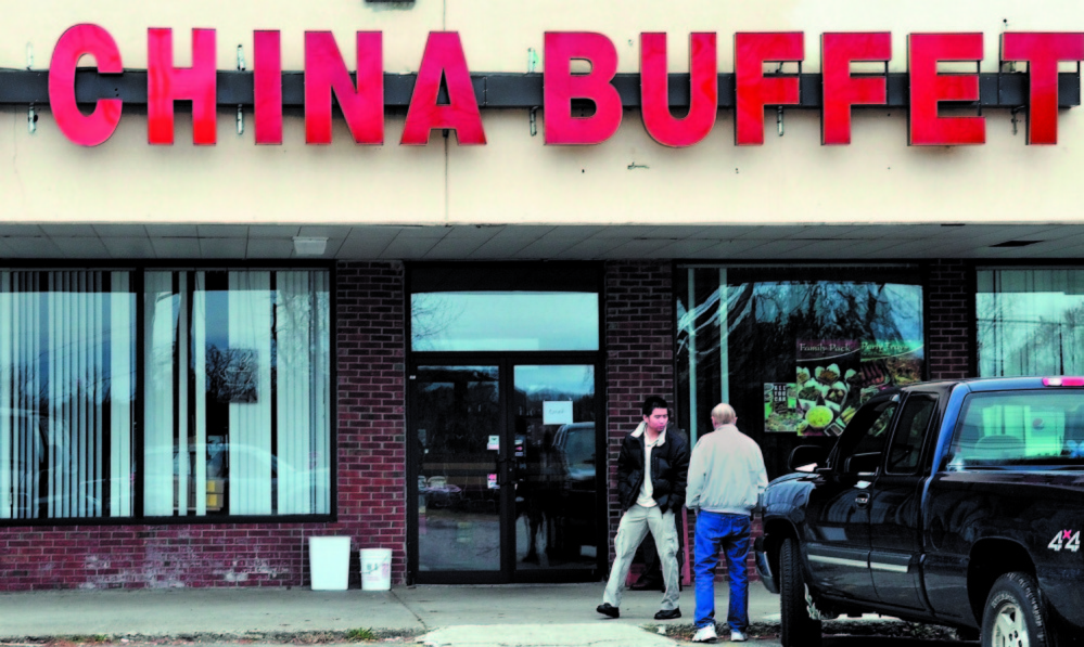 An employee and a U.S. Immigration and Customer Enforcement agent stand outside the Super China Bufet Restaurant in Waterville in November, 2011. The restaurant was one of several owned by a Massachusetts couple throughout New England. On Tuesday, a second niece of the restaurant owners was sentenced to federal prison for illegally employing immigrants in a restaurant owned by family members in Brewer.