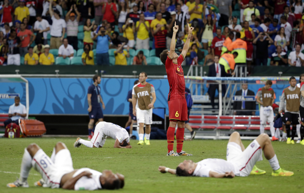 Exhausted US players lie on the ground as Belgium's Axel Witsel celebrates at the end of the extra time after Belgium beat the US 2-1 in the knockout round of the World Cup on Tuesday in Salvador, Brazil.