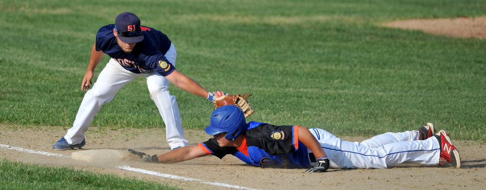 RTD of Madison's Kam Nelson, 12, dives back to first base before Post 51's Zach  Mathieu, 9, can apply the tag at first base at Colby College Tuesday. RTD defeated Post 51 5-2.