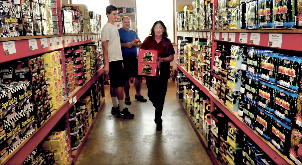 Pyro City store employee Lyla Carlow brings a fireworks package to the counter as Bert Languet and his son Jose select more at the Winslow fireworks business on Tuesday.