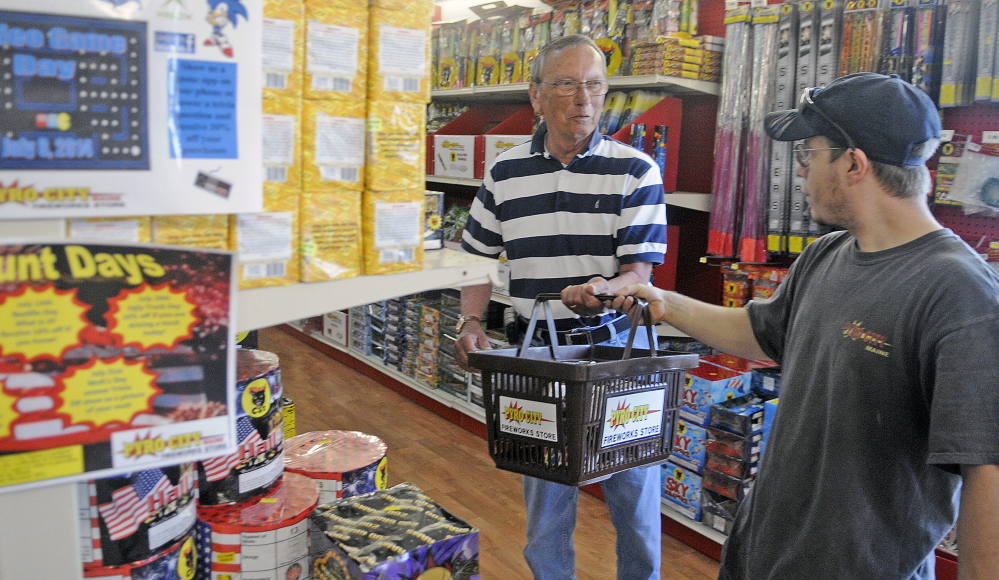 Pyro City retail store employee Brandon Pelletier, right, hands customer Bill Dowling of Augusta a container of fireworks Tuesday at the outlet in Manchester.