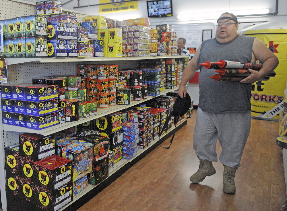 """John Bergen of Somerville carries rockets Tuesday from the Pyro City retail store in Manchester. Bergen, a professional explosives engineer, said safety is paramount. """"It's up to the individual to keep it safe so we all can enjoy the tradition,"""" Bergen said."""