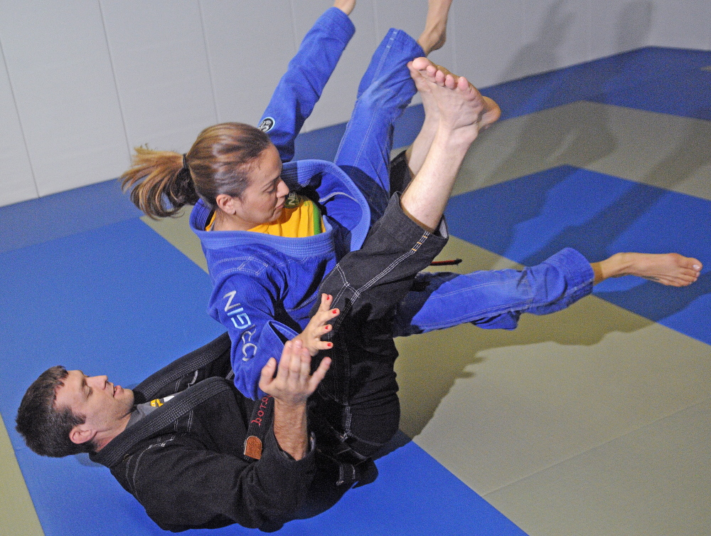 Jarod Lawton flips his wife, Marcela Lawton, while practicing  martial arts Monday at their Farmingdale gym, Innovative Athletics Martial Arts. The couple fight in professional mixed martial arts competitions.