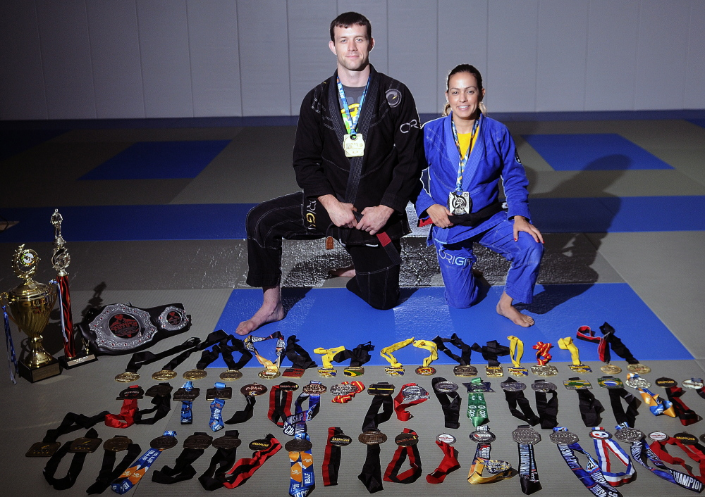 Jarod and Marcela Lawton display some of the medals they have won at their Farmingdale gym, Innovative Athletics Martial Arts.  The couple fight in professional mixed martial arts competitions.