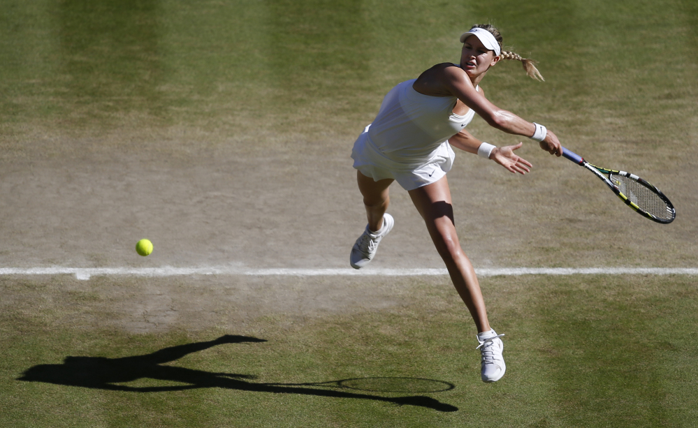 Eugenie Bouchard of Canada leaps as she plays a rerun to Simona Halep of Romania during their women's singles semifinal match at the All England Lawn Tennis Championships in Wimbledon, London, on Thursday.