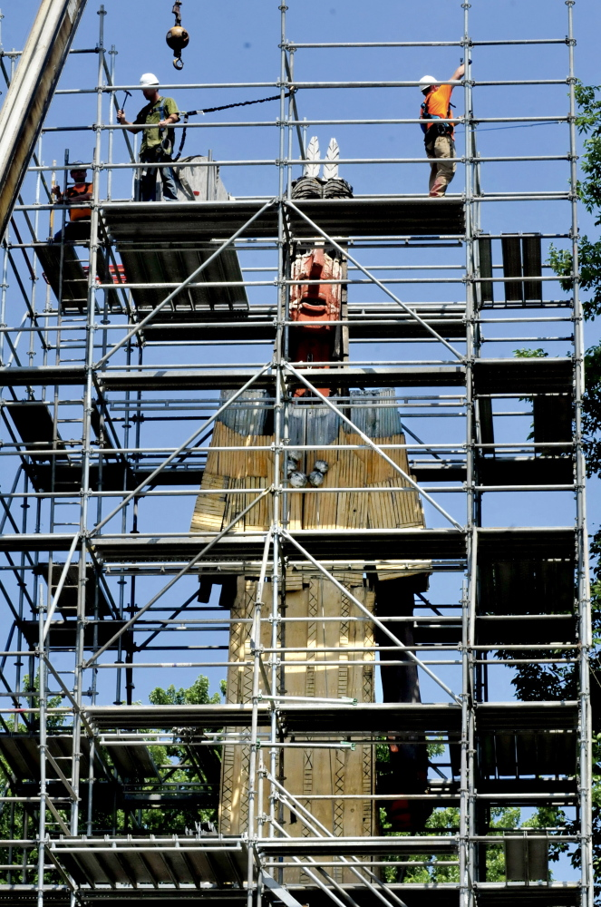 Workers from Seacoast Scaffolding erect scaffolding around the Skowhegan Indian statue for restoration of the aging piece. The arm at left is missing and there are several holes and rotted wood throughout the artwork.