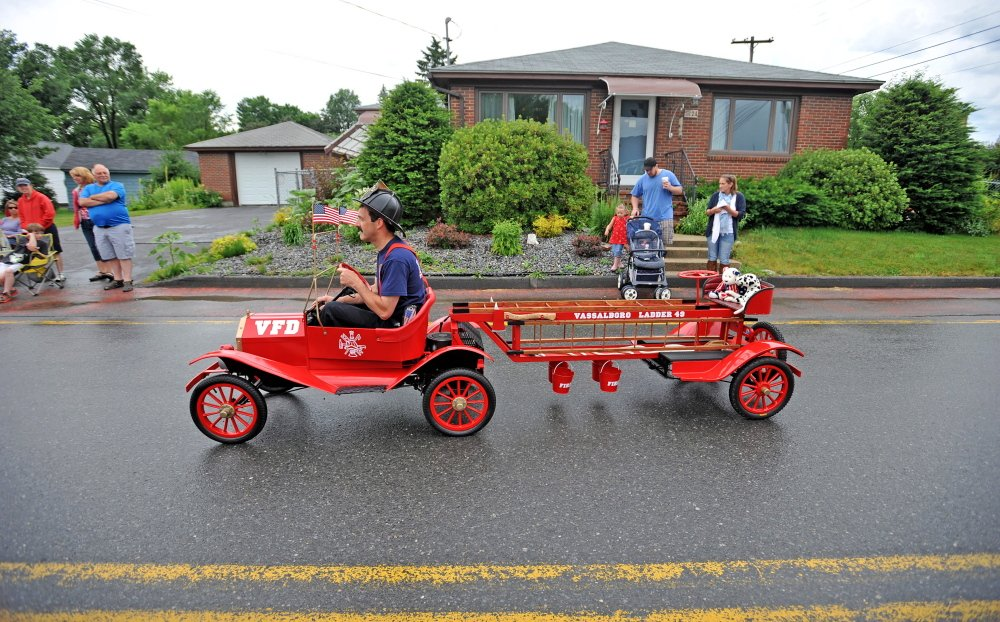 A Vassalboro Fire Department firefighter drives a tiny vehicle along North Garand Street in the Wnslow Family 4th of July Celebration parade on Saturday.