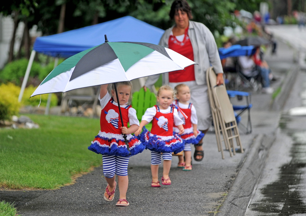 Sera Dixon, 4, leads her 2-year old twin sisters, Keira, center, and Joslin, back, with mother Shannon Dixon, far back, to a parade viewing spot on North Garand Street next to Winslow High School on Saturday. The annual Winslow Family 4th of July Celebration parade had postponed until Saturday because of rain on Friday.