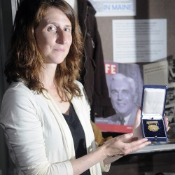 "Curator Kate McBrien, at the Maine State Museum in Augusta, holds a medal of valor that Donn Fendler received from President Franklin Roosevelt in 1939. This year is the 75th anniversary of Fendler surviving on Mount Katahdin, an ordeal later chronicled in the book ""Lost on a Mountain in Maine."" The museum is exhibiting items from Fendler's saga."