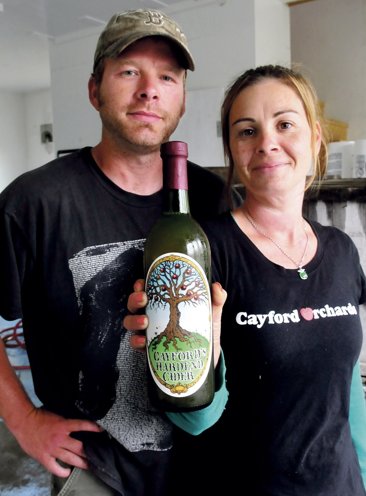 Jason and Heather Davis hold a bottle of Cayford's Hardened Cider, which they make at their business, Cayford's Orchards.