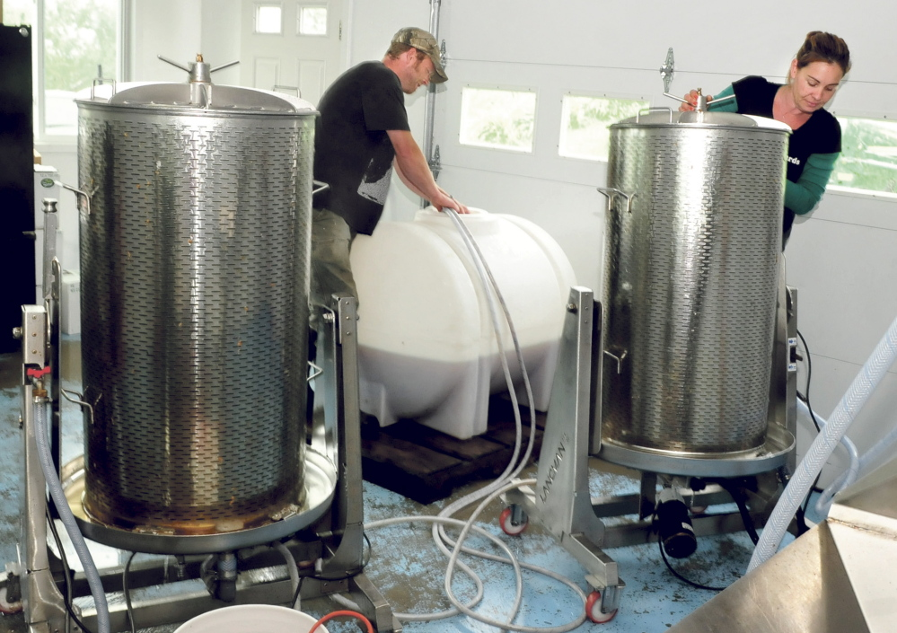 Jason and Heather Davis work around equipment as apple syrup processes in tanks Thursday at Cayford's Orchards in Skowhegan. The Davises have diversified. In addition to making cider, they now make hard cider and apple syrup and soon will make apple vinegar.
