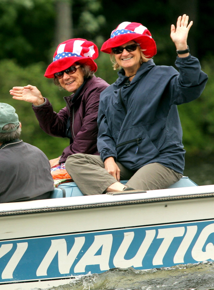 Boaters wave to a crowd lined up along Mill Stream on Saturday to watch the annual boat parade to celebrate Independence Day in Belgrade Lakes village.