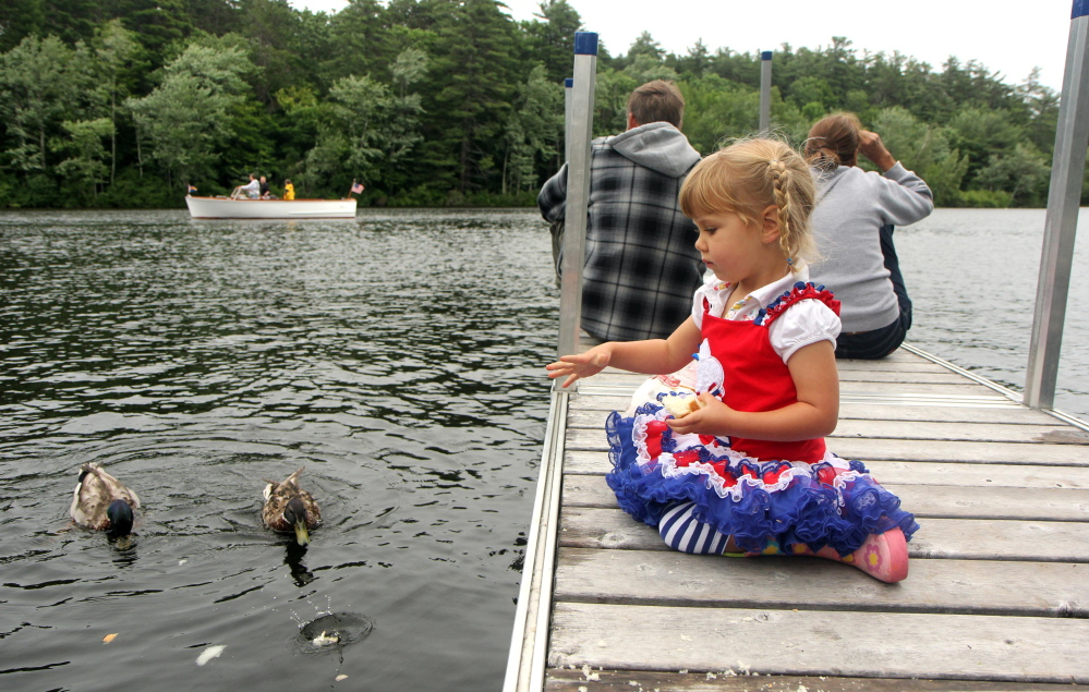 Sunniva Saal, 2, of Rome feeds some ducks Saturday as pectators take in the annual boat parade to celebrate Independence Day in Belgrade Lakes village.