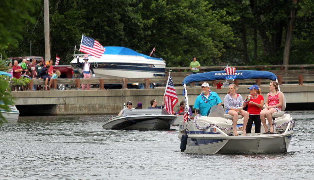 Boaters make their way up Mill Stream on Saturday during the annual boat parade to celebrate Independence Day in Belgrade Lakes village. The event was postponed a day.
