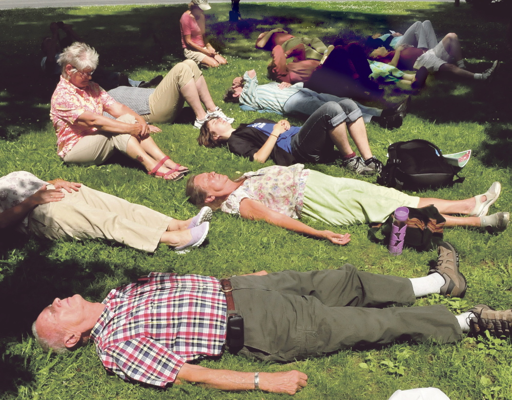 Nearly forty people took part in a memorial at the Universalist Unitarian church in Waterville on Sunday, July 7, 2014, for the 47 victims of the Lac Megantic train tragedy. Participants, including Richard Dillenbeck, front, were asked to lie down in remembrance of the victims who perished in the oil train inferno.
