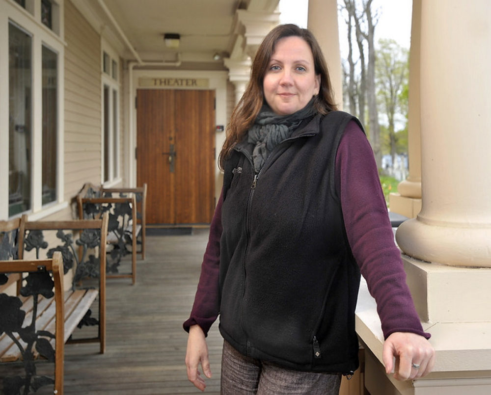 Dawn McAndrews, the producing artistic director at the Theater at Monmouth stands on the veranda entrance to the theater, graced with large columns.