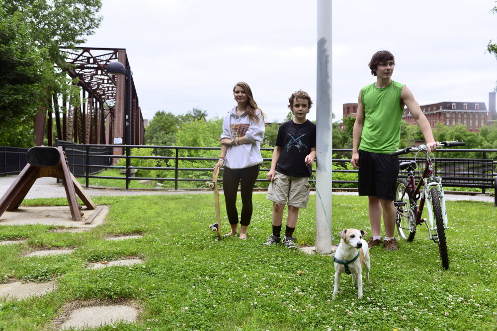 Tessa Kunz (from left), Garret Blackerby, Laughing Sprucebarns and their dog Bean near the Riverwalk Bridge on Thursday, June 26, 2014. Kunz lives in Auburn and Blackerby and Sprucebarns both live in Lewiston. The kids are in favor of merging the cities, and they hope it would lead to better parks and safer neighborhoods in Lewiston.