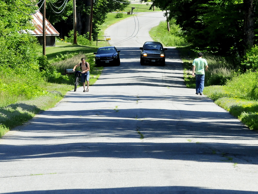 Though closed to all but local traffic, a pedestrian, cyclist and a motorist used the Morrison Hill Road in Farmington on Tuesday. The extremely rough road, named one of five worst roads in town, had a large culvert replaced as part of a major upcoming reconstruction.