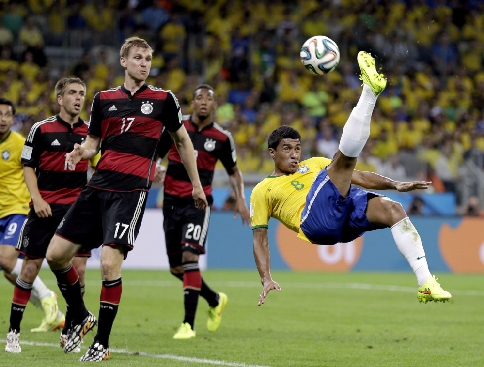 Brazil's Paulinho (8) kicks the ball in front of Germany's defenders during the World Cup semifinal Tuesday in Belo Horizonte, Brazil.