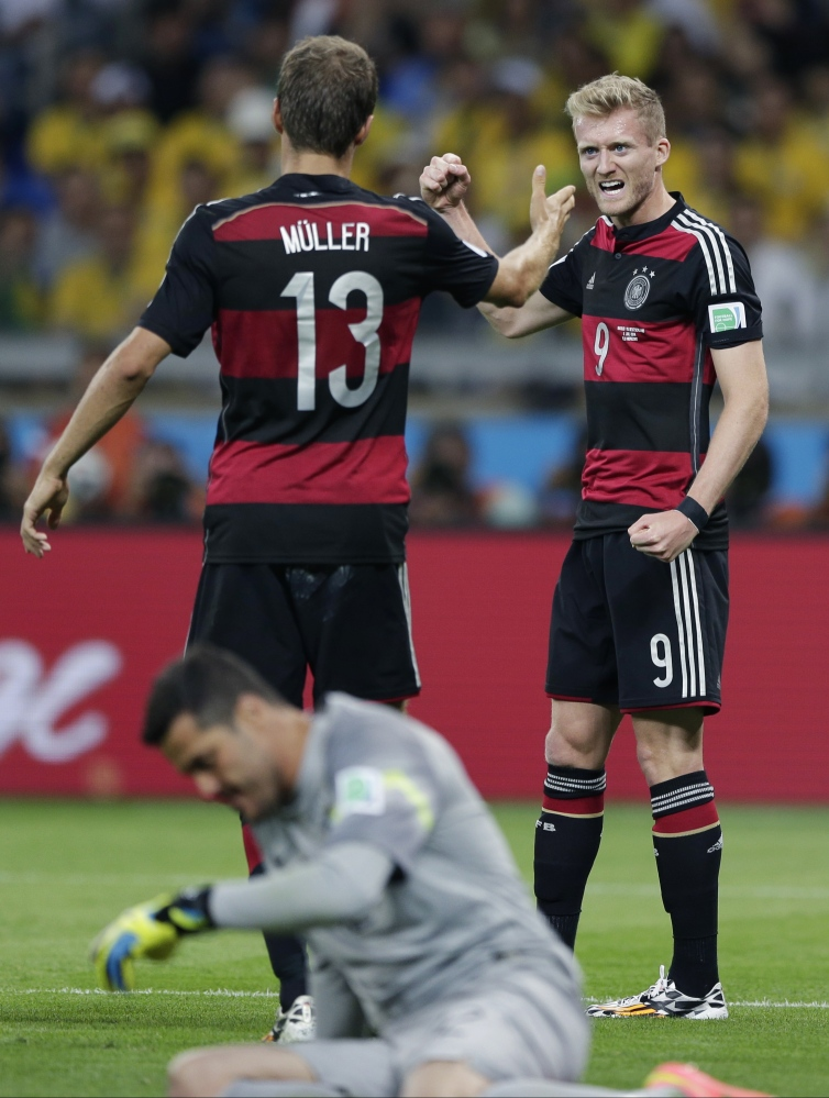 Germany's Andre Schuerrle, right, celebrates with Thomas Mueller after scoring his side's sixth goal during the World Cup semifinal soccer match between Brazil and Germany at the Mineirao Stadium in Belo Horizonte, Brazil, Tuesday.