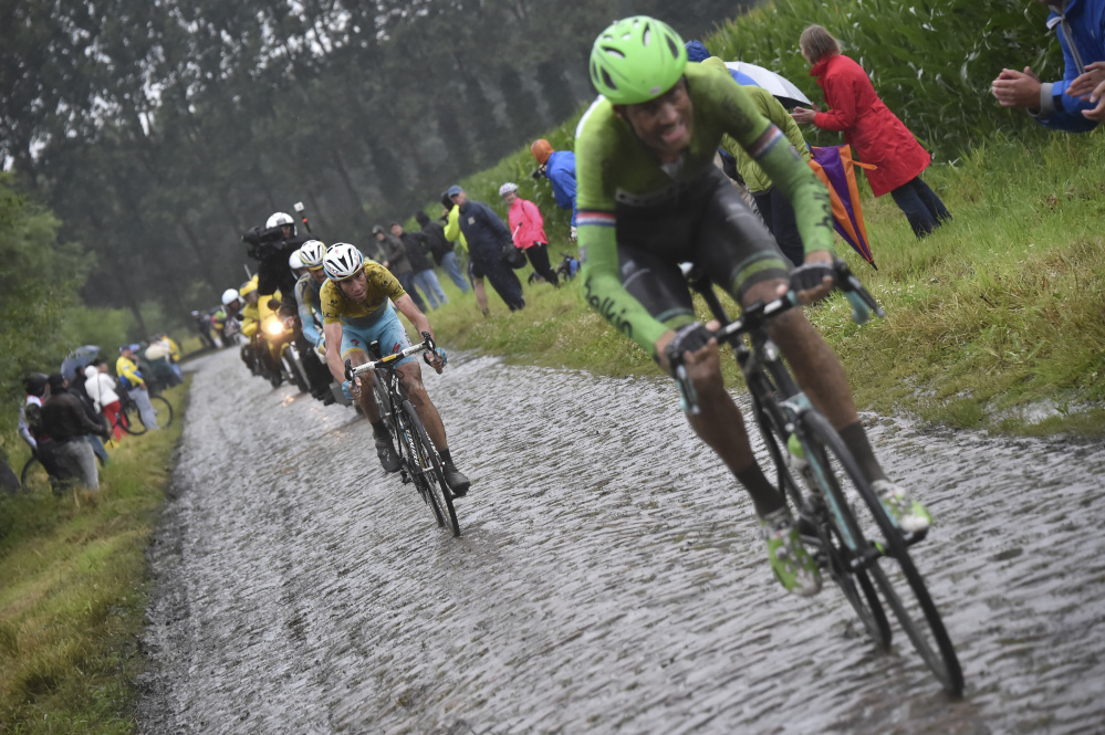 Italy's Vincenzo Nibali, wearing the overall leader's yellow jersey, rear, is unable to keep the pace as stage winner Lars Boom of The Netherlands breaks away during the fifth stage of the Tour de France cycling race over 155 kilometers (96.3 miles) with start in Ypres, Belgium, and finish in Arenberg, France, Wednesday.