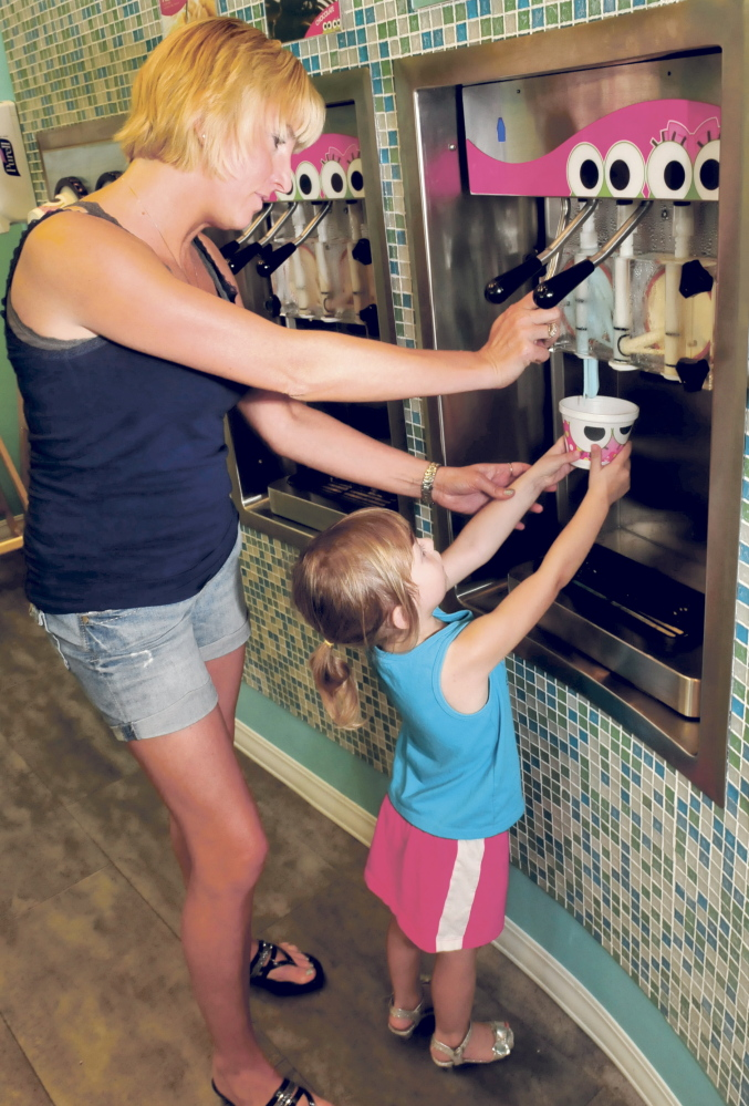 Jeanne Garza helps her daughter Rosabella pour her choice of frozen yogurt Wednesday at the new sweetFrog store in Waterville.