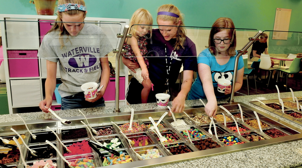 Customers pile on some of the 70 toppings available Wednesday at the new sweetFrog store in Waterville. From left are Leah Shoulta, Roselia Bowling, Sarah Shoulta and Sarah Holderman.