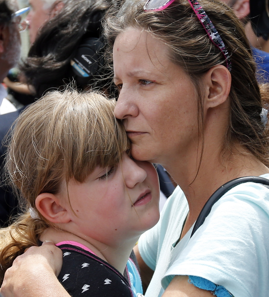 Geri Boyles of Lowell, Mass., hugs her daughter, Corinna, 10, outside a burned three-story apartment and business building in Lowell, Mass., on Thursday. The neighbors lost people they knew in the fast-moving pre-dawn fire where officials said seven people died.